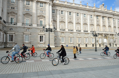 MADRID, SPAIN - MARCH 3, 2014  Tourists on bicycles on Plaza de Oriente against Royal Palace in Madrid  Madrid is a popular tourism destination with average about of 4 million estimated annual visitors