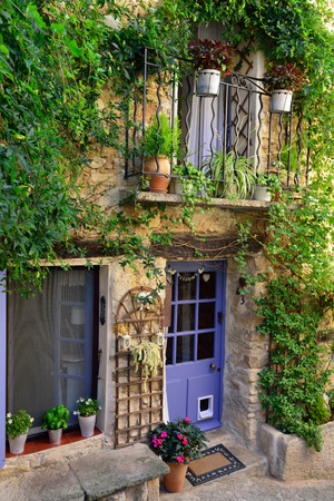 France, Provence  Typical medieval street with a house surrounded a green plant   photo