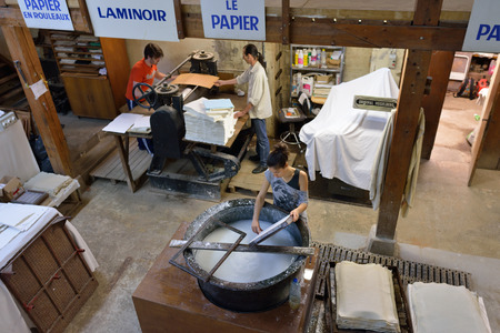 fontaine: PROVENCE, FRANCE - JUL 8, 2014: Workers made a paper in medieval paper mill in Village of Fontaine de Vaucluse. Local manufacturing was founded in the 14th century Editorial