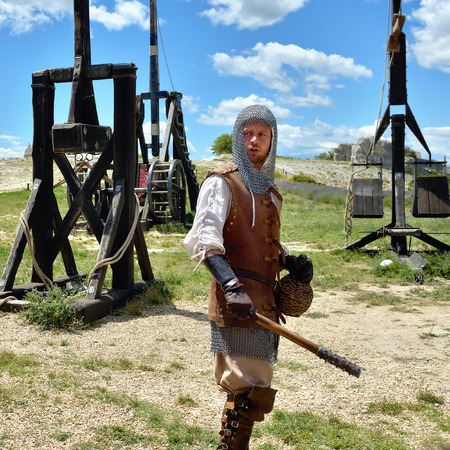 catapults: LES BAUX, FRANCE - JUL 9, 2014: Actor dressed as medieval warrior perform the show near the catapults. Les Baux is now given over entirely to the tourist trade, historical show is part of entertainment Editorial