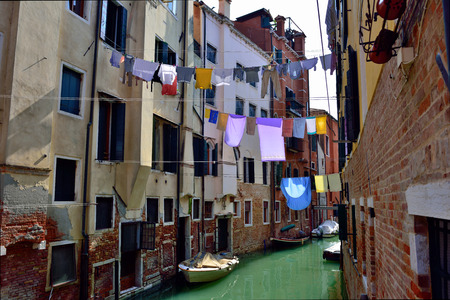 Venice, Cannaregio, Ghetto Ebraico. Dried dress over water canal in Jewish Ghetto. Tourists from all the world enjoy the historical city of Venezia in Italy