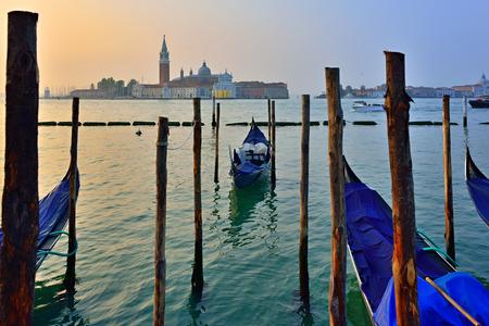 saint mark square: Gondolas moored by Saint Mark square with San Giorgio di Maggiore church in the background at sunrise - Venice, Italy, Europe