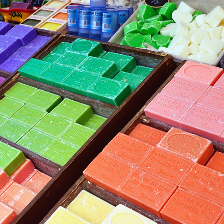 PROVENCE, FRANCE - JULY 6, 2014: French soap in various color displayed in a street market in public street. Local soap the most popular souvenir in Provence