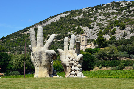 agricultura: PROVENCE, FRANCE - JULY 11, 2014: Modern sculpture - peasant hands with grapes. Provence is one of the largest agricultural regions in France Editorial