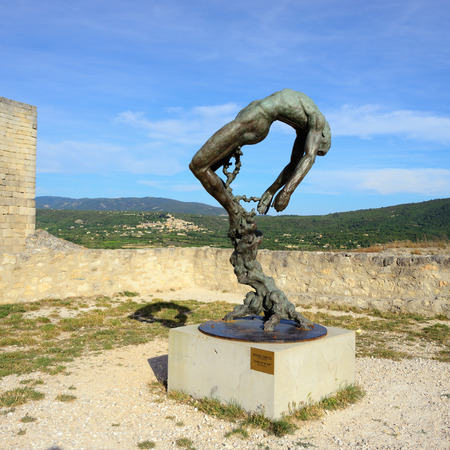 LACOSTE, FRANCE - JUL 11, 2014:  Statue of Marquis de Sade in front of Provence landscape. The terms sadist and sadism are derived from Marquis de Sade