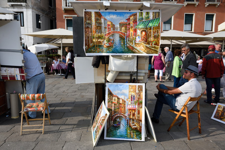 VENICE, ITALY - SEP 24, 2014: Unknown artist sells paintings on the waterfront in Venice. Tourists from all the world enjoy the historical city of Venezia in Italy, famous UNESCO World Heritage Site