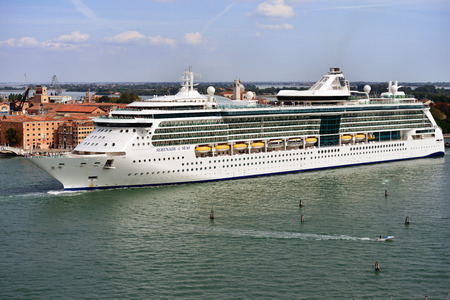 VENICE, ITALY - SEPT 24, 2014: The luxury cruise ship shown in the Venetian Lagoon at morning. More than 10 million tourists visit Venice every year Imagens - 34360588