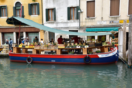 local business: VENICE - SEPT 25, 2014. Fruit and vegetable stall on boat on canal on October 28, 2009 in Venice, Italy. The population of Venice decreases yearly making local business increasingly difficult.