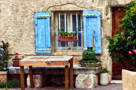 rose window: France, Provence, Villes-sur-Auzon village. Beautiful facade of medieval house with decorated window and old wooden shutter painted in traditional blue color surround a green plant. Filtered image