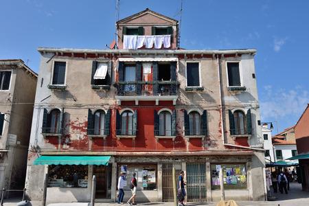 Murano: MURANO - SEP 22, 2014: Tourist walking along facade on the typical building at Murano island, Venice. Landmark of Veneto region, Italy