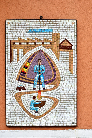 glassblower: MURANO ISLAND, ITALY - SEPT 26, 2014: Colorful mosaic on the street of Murano. Craftsman - glassblower making glassware - symbol of independence of the island