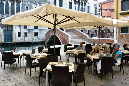 VENICE, ITALY - SEPT 21, 2014: People visit street cafe on in Venice at morning time. This is the typical Venetian cafe Editorial