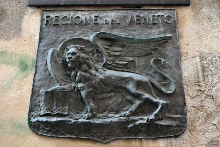 leon con alas: Le�n alado veneciano - el s�mbolo de la ciudad, un bajorrelieve de bronce en la fachada de un edificio en Venecia, Italia