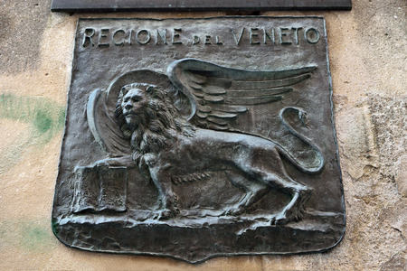 winged lion: Venetian winged lion - the symbol of the city, a bronze basrelief on the facade of a building in Venice, Italy Stock Photo