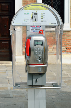 payphone: VENICE, ITALY - SEP 21, 2014: Modern public phone box in Venice. More that ten millions tourists from all the world visit the historical city Venice in Italy, famous UNESCO World Heritage Site Editorial