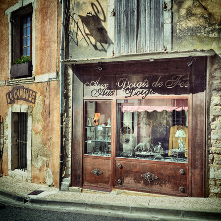 cited: BONNIEUX, FRANCE - JUL 11, 2014: Decorated window of antique shop on the street of the beautiful  village of Bonnieux. Bonnieux is included in list of The most beautiful villages of France. Filtered image
