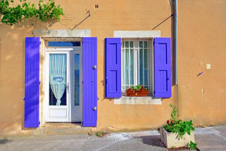abrir puerta: Abrir puertas y ventanas con persianas de madera de color lavanda en color ocre enyesados ??pared en un d�a soleado. Pueblo de Bonnieux, Provenza, Francia