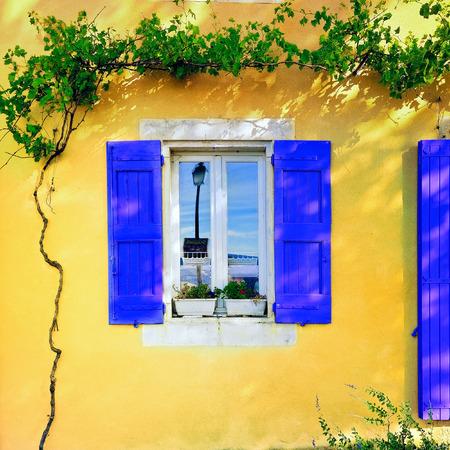 黄土色の色にラベンダー色の木製シャッターの開いているウィンドウは、晴れた日に壁を漆喰しました。ボニューの村、プロヴァンス、フランス