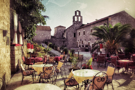 Empty coffee terrace with tables and chairs in old town of Budva on sunny day at sunset, Montenegro. Filtered image, vintage effect applied. Grunge Editorial