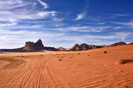 described: Wadi Rum desert landscape at sunset time, Jordan. View on the cliff called Seven Pillars of Wisdom which described in book of the British officer Lawrence of Arabia
