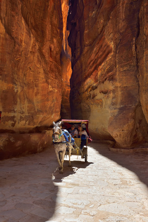 proportions of man: PETRA JORDAN APR February 2015: Unidentified people in a horse carriage in a gorge Siq canyon in Petra Jordan