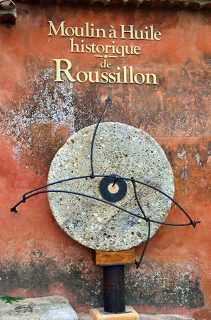 millstone: Millstone from olive oil press moulin a huile in Roussillon. That ocher village is included in list of Stock Photo