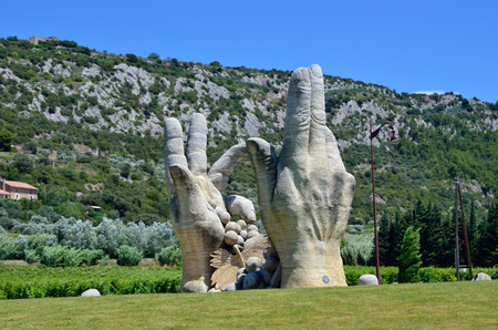 agricultura: PROVENCE FRANCE JULY November 2014: Modern sculpture peasant hands with grapes. Provence is one of the largest agricultural regions in France
