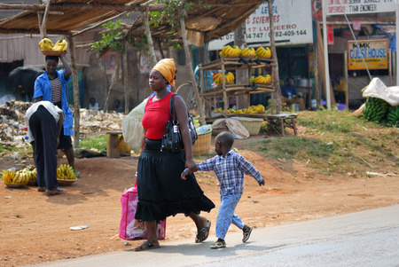 KAMPALA UGANDA AUG 26 2010: Local woman with her son shown in slum of Kampala. Nearly 40 of slum dwellers have a monthly income of just 2500 shillings less than a dollar Editorial