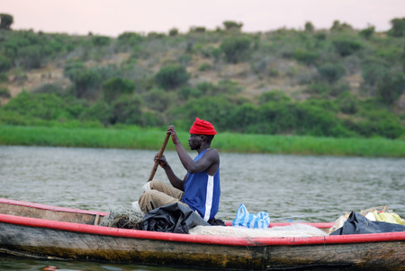 UGANDA - AUG 29, 2010: Fisherman in a boat moving on the Victoria Nile at twilight. The Nile river is the only source of transportation in this region of central Africa