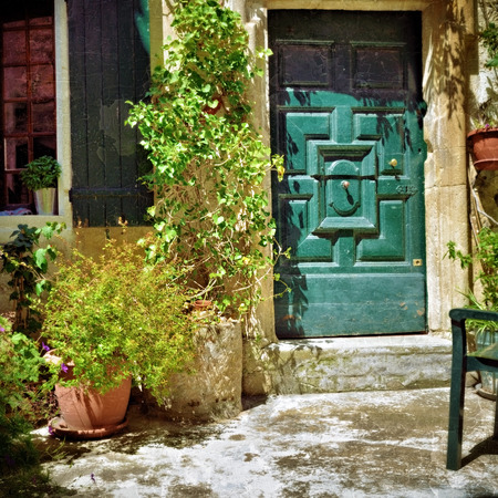 romaine: France, Provence. Vaison la Romaine. Typical medieval houses decorated with green plant and flowers in pots. Filtered image, vintage effect applied Editorial