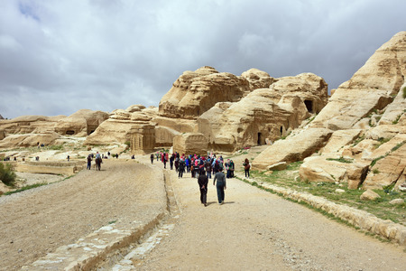 siq: PETRA, JORDAN - APR 1, 2015: Tourists walking to Siq canyon in Petra. Petras temples, tombs, theaters and other buildings are scattered over 400 square miles. Editorial