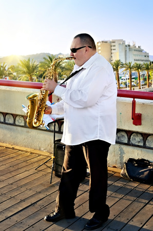 jewish town: EILAT, ISRAEL - MARCH 31, 2015:  Unidentified musician performs in the street in Eilat at sunset. This is one of the popular for outdoor performances in Eilat Editorial
