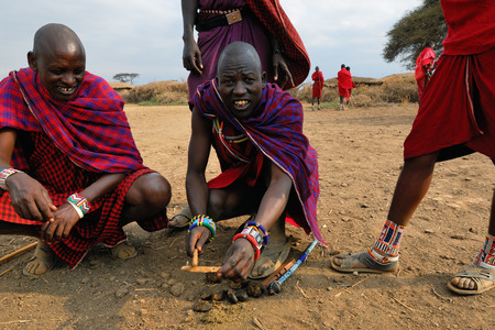 african warriors: MASAI MARA, KENYA - AUG 23, 2010: An unidentified men from Masai tribe showing how they make fire in a traditional way from donkey droppings to guests visiting their village Editorial