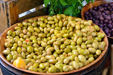 olive green: Marinated green and black french olives in big pot at the rural market. Provence, France Stock Photo