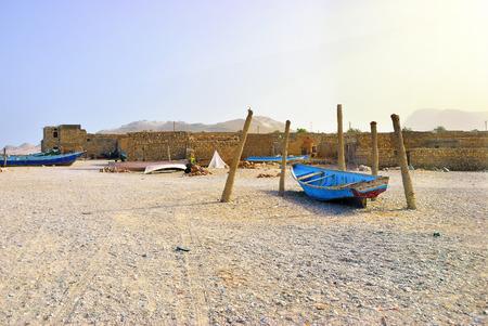 sund: Blue fishing boat on the ocean shore at Socotra island, Yemen. Warm evening light