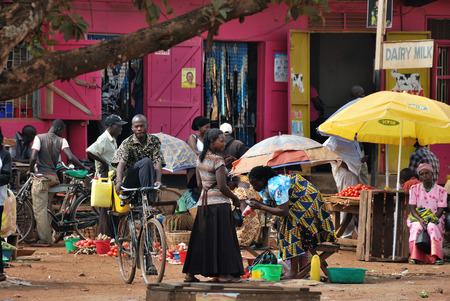 squalor: FORT PORTAL, UGANDA - AUG 28, 2010: Local people make a purchase on the street market. Nearly 40 of slum dwellers have a monthly income of just 2,500 shillings less than a dollar Editorial