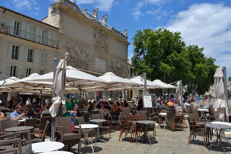 avignon: AVIGNON, FRANCE - JULY 12, 2014: Tourists in the street cafe.  A lot of tourists visit Avignon during the annual Avignon Theater Festival in Avignon.