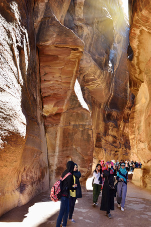 siq: PETRA, JORDAN - APR 2, 2015: Tourists walking in Siq canyon in Petra. UNESCO world heritage site and one of The New 7 Wonders of the World. Editorial