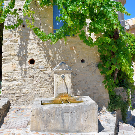 hot water tap: Public tap water device on the facade, covered a green wild vine, of the old stone house in beautiful medieval village Vaison la Romaine on hot summer day. Provence, France Stock Photo