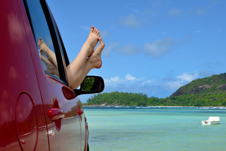 dangling: A place of a destination. Womans legs dangling out a car window parked at the beach Stock Photo