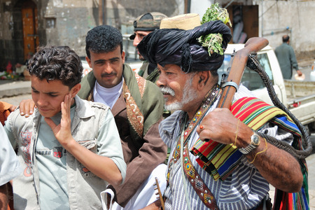 gad: SANAA, YEMEN - MAR 6, 2010: Armed antique rifle senior man among people on the street in old city of Sanaa. Inhabited for more than 2.500 years, the Old City of Sanaa is now destroyed by the civil war Editorial