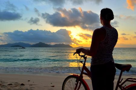 아름다운 일몰을 감상 해변에서 자전거 소녀입니다. 황혼에서 실루엣입니다. 세이셸 섬 라 줘 봐 스톡 콘텐츠