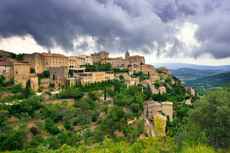 cited: Beautiful Medieval Village of Gordes under dramatic sky before thunderstorms, Provence, France. Stock Photo