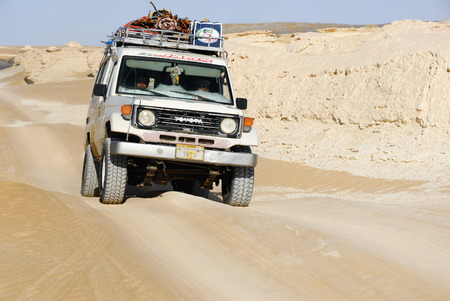desierto: EGIPTO, SAHARA - 26 de diciembre 2008: Coche campo a través se muestra en el desierto valle Carpa. Safari por el desierto Extreme es una de la principal atracción turística local en Egipto