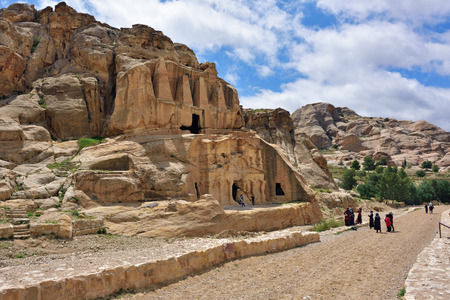 bab: PETRA, JORDAN - APR 1, 2015: Tourists walking around Bab Al-Siq tomb in Petra. Petras temples, tombs, theaters and other buildings are scattered over 400 square miles. Editorial