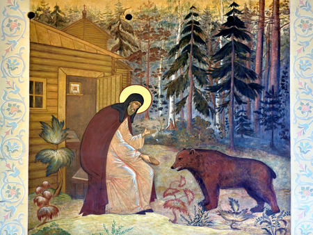 SERRGIEV POSAD, RUSSIA - OKT 16, 2015: Masterpiece of ancient russian art - Hermit and bear. Religious painting on a church facade in Trinity Sergius Lavra. UNESCO World Heritage Site.