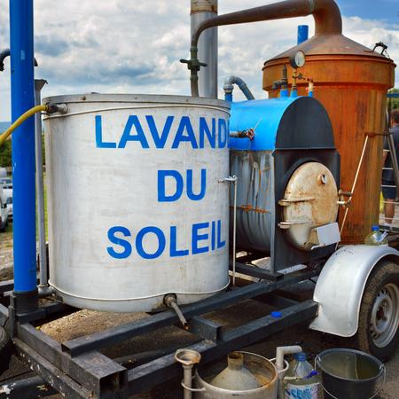 """destilacion: retro aparato para la destilación de aceite de lavanda en un mercado rural en Provence, Francia. Título en el tanque """"Lavanda du Soleil"""" significa """"Lavanda Sun"""" Foto de archivo"""