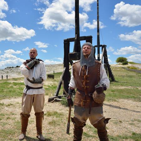 castello medievale: Les Baux, Francia - 9 luglio 2014: Amateur ricostruzione storica di guerre medievali. Mens vestiti da guerrieri medioevali stand vicino la catapulta. castello di Les Baux