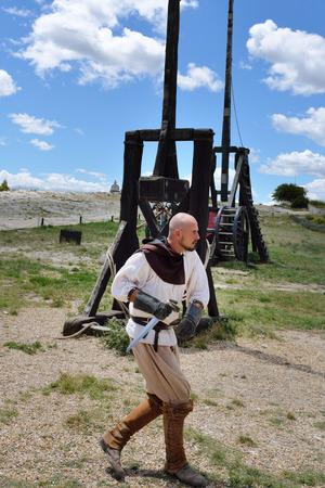 catapults: LES BAUX, FRANCE - JUL 9, 2014: Amateur historical reconstruction of medieval wars. Man dressed as medieval warrior runs along the catapults. Les Baux castle