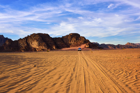 Traces from cars in the Wadi Rum (Moon Valley) desert shown at sunset time, Jordan Stock Photo
